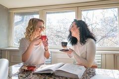 Zwei Mädchen trinken Kaffee und lachen im Café lizenzfreie stockbilder