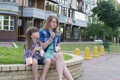 Zwei Mädchen auf dem Straßensnack lizenzfreies stockbild