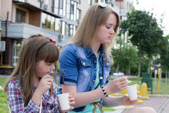 Zwei Mädchen auf dem Straßensnack stockbild