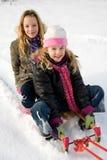 Zwei Mädchen auf einem Schlitten Stockbild