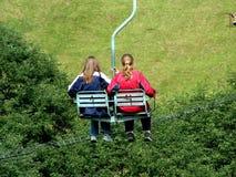 Zwei Mädchen auf einem Sessellift im Sommer. Lizenzfreies Stockbild