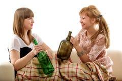 Zwei Mädchen auf einem Sofa, nachdem Wein getrunken worden ist Stockfotografie