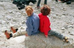 Zwei Mädchen auf einem Stein stockfotografie