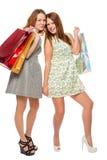Zwei Mädchen auf einem weißen Hintergrund mit Taschen Lizenzfreie Stockfotografie