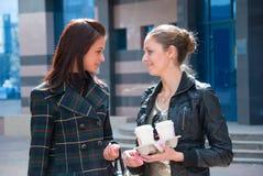 Zwei Mädchen auf einer Straße mit Kaffee Lizenzfreie Stockfotografie