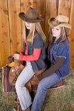 Zwei Mädchen auf Sattel mit Hüten Lizenzfreie Stockbilder