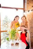 Zwei Mädchen bereiteten eine verpackte Geschenkbox für ihren Geburtstagsfreund vor, Stockfotos