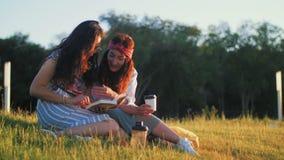 Zwei Mädchen besprechen ein interessantes Buch stock video