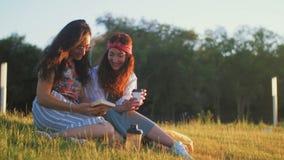 Zwei Mädchen besprechen ein interessantes Buch und einen trinkenden Kaffee stock footage