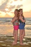 Zwei Mädchen blond auf dem Strand am Sonnenuntergang Lizenzfreie Stockbilder