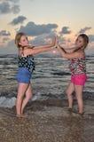 Zwei Mädchen blond auf dem Strand am Sonnenuntergang Stockfotos
