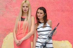 Zwei Mädchen Brunette und blonde Frau mit dem langen Haar, das gegen Graffitihintergrund aufwirft Lizenzfreie Stockbilder