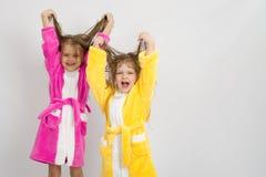 Zwei Mädchen in den Bademäntel hoben ihr nasses Haar an stockfotos