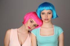 Zwei Mädchen in den bunten Perücken, die zusammen stehen Abschluss oben Grauer Hintergrund lizenzfreie stockfotografie