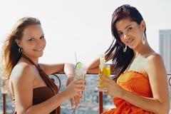 Zwei Mädchen an den Feiertagen in Kuba, Cocktails anhalten Stockfotos