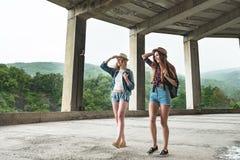 Zwei Mädchen in den Hüten, die durch Ruinen reisen stockfoto