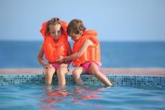 Zwei Mädchen in den Schwimmwesten, die auf Leistepool sitzen Stockfotografie
