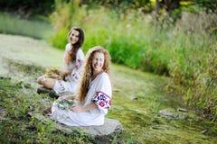 Zwei Mädchen in den ukrainischen Hemden sind auf dem Hintergrund des Flusses Lizenzfreies Stockbild