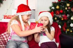 Zwei Mädchen in den Weihnachtskostümen, die auf sitzen Lizenzfreie Stockfotografie