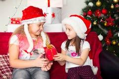 Zwei Mädchen in den Weihnachtskostümen, die auf sitzen Lizenzfreies Stockfoto