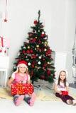 Zwei Mädchen in den Weihnachtskostümen, die unter sitzen Stockbild