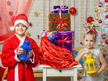 Zwei Mädchen in den Weihnachtskostümen sind- mit Kerzenständern von der Tasche mit Weihnachtsgeschenken Stockbild