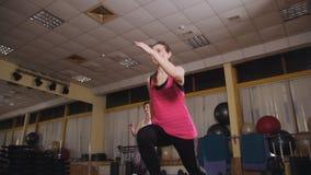 Zwei Mädchen in der aeroben Handelnstepp-aerobic der Sporthalle stock video