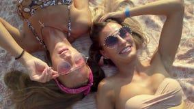 Zwei Mädchen in der Sonnenbrille, die den Spaß liegt auf Strand hat stock footage