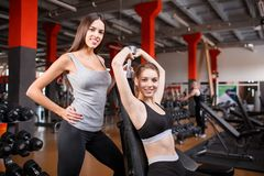 Zwei Mädchen in der Turnhalle lächeln, eins von ihnen mit Dummköpfen Lizenzfreie Stockfotos