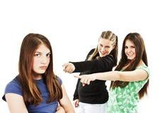 Zwei Mädchen, die über einem Mädchen sich lustig machen lizenzfreies stockfoto