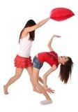 Zwei Mädchen, die auf den Kissen kämpfen Stockfoto
