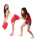 Zwei Mädchen, die auf den Kissen kämpfen Lizenzfreies Stockfoto