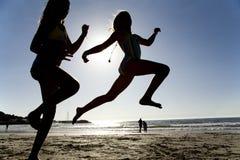 Zwei Mädchen, die auf den Strand springen Lizenzfreies Stockfoto