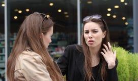 Zwei Mädchen, die auf der Bank sprechen Stockfoto