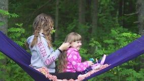 Zwei Mädchen, die auf der Hängematte spielen stock video