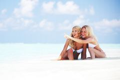 Mädchen, die auf Ozeanküste sitzen Stockfotografie