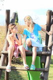 Zwei Mädchen, die auf Dia sprechen Stockbild
