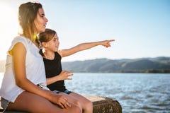 Zwei Mädchen, die auf Dock und dem Zeigen sitzen Lizenzfreies Stockfoto