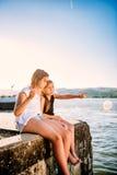 Zwei Mädchen, die auf Dock und dem Zeigen sitzen Lizenzfreie Stockbilder
