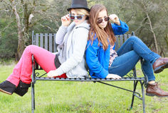 Zwei Mädchen, die auf eine Bank einstellen Stockfotografie
