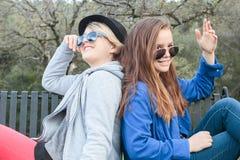 Zwei Mädchen, die auf eine Bank einstellen Stockfotos