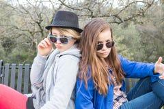 Zwei Mädchen, die auf eine Bank einstellen Lizenzfreie Stockfotografie