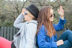 Zwei Mädchen, die auf eine Bank einstellen Lizenzfreie Stockfotos