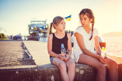 Zwei Mädchen, die auf einem Dock sprechen und sitzen Stockbild