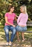 Zwei Mädchen, die auf einer Bank sprechen Lizenzfreies Stockfoto