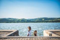 Zwei Mädchen, die auf Flussdock stehen und seitlich schauen Lizenzfreies Stockfoto