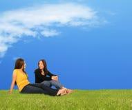 Zwei Mädchen, die auf Gras sich entspannen Lizenzfreie Stockfotos