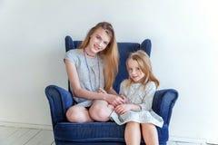 Zwei Mädchen, die auf modernem blauem Stuhl sitzen stockbild