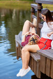 Zwei Mädchen, die auf Pier sich entspannen Stockfotos