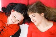 Zwei Mädchen, die auf rotem Kissen liegen Stockfotografie